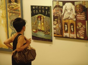 A visitor considers the Alice display - photo courtesy of The Art League