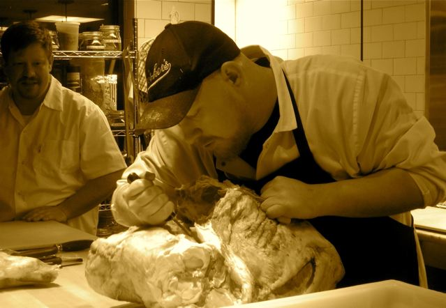 Chef Will Harlan breaks down a side of beef while Chef/Owner Scott Harlan looks on at Green Pig Bistro - photo credit Jordan Wright