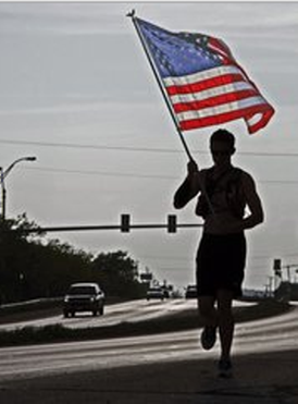 Alexandria resident Brendan O'Toole carries a U.S. flag during his run through West Texas in honor of the victims of the Boston Marathon bombing earlier - Photo by Tim Dwyer