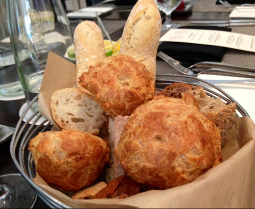 A basket of gougeres and assorted in house baked breads