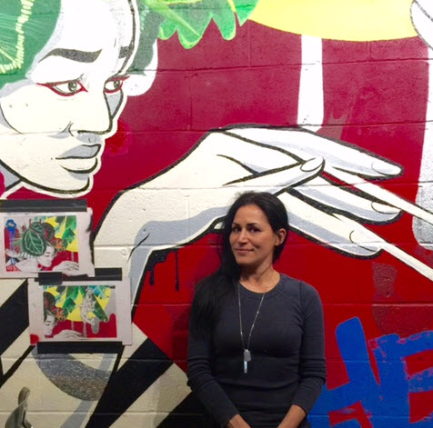 Brazilian Muralist Miss Chelove poses with her latest creation
