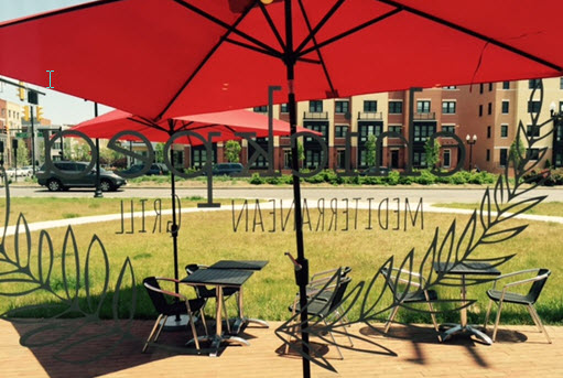 Bright red umbrellas punctuate the patio seating at Chickpea