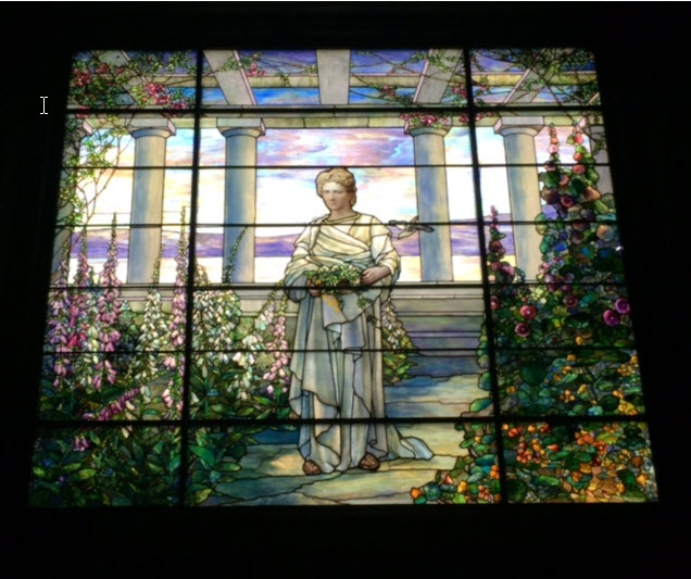 A Tiffany window at the top of the grand stairway portrays Sallie May Dooley in her gardens at Swannanoa