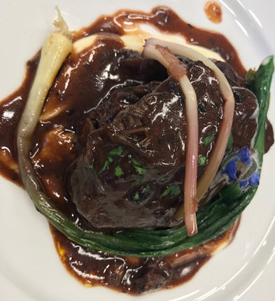 Braised Beef Cheeks over Celery Root Purée with Truffle Triple Sauce & Pickled Ramps garnished with borage flower