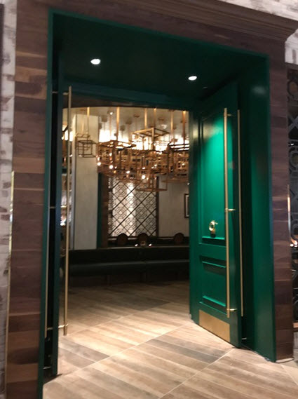 Malachite green doors beckon diners to relax beside a fireplace at Isabella Eatery
