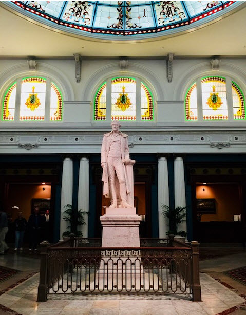 Carrara marble statue of Thomas Jefferson amid Tiffany windows in the Palm Court lobby