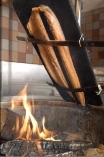 Cedar-planked Juniper Salmon over the fire pit at Mitsitam Café – (credit to the Café at National Museum of the American Indian)